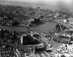 Aerial View of Destroyed City of Manila, 1945.Vividly illustrating the condition of burned-out, battle-scarred Manila, as U.S. engineers and thousands of Filipinos begin the huge task of reconstruction, in this aerial view looking southwest across the Pasig River toward hulks of sunken ships in the Manila Harbor. Tall building, left foreground, is gutted, Great Eastern Hotel, center, across river, is burned out, Post Office Building, extreme left, across river is Metropolitan Theater in…