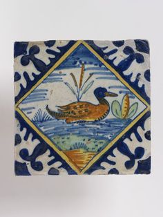 Tile, square, depicting a duck within a lozenge-shaped frame, the intervals being filled with stylised foliage in reserve against a blue ground.  1620-40