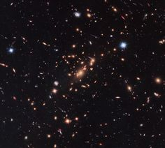 """Hubble Uses Gravitational Lens to Capture Disk Galaxy By combining the power of a """"natural lens"""" in space with the capability of NASA's Hubble Space Telescope astronomers made a surprising discoverythe first example of a compact yet massive fast-spinning disk-shaped galaxy that stopped making stars only a few billion years after the big bang."""