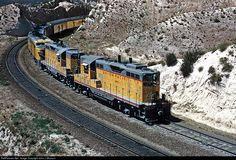 """A pair of Union Pacific GP7s, 119 and 114, assist a passenger train over southern California's Cajon Pass. The eastbound passenger train, most likely train #10, the """"Domeliner"""" (Los Angeles CA to Saint Louis, MO), is led by an A-B-A set of PA-1s. Interestingly, this train was numbered #210 while on the Santa Fe from Riverside to Daggett, over which the UP has trackage rights. The two GPs were built in summer 1953 as 719 and 714, and they were renumbered to 119 and 114 just a few months…"""