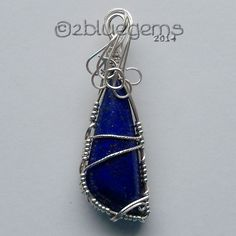 """This beautiful free form, dark blue Lapis Lazuli cabochon is wrapped in Sterling Silver wire. The wire drapes over the top of the cab in a wave of silver, enhancing the richness of the blue of the Lapis.    The overall measurements of the pendant are 2 1/4"""" tall by 3/4"""" wide.  It will come on a..."""
