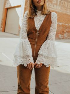 Fashion blogger Emily Vartanian layers right with a white lace blouse under a corduroy jumpsuit