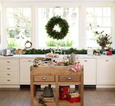 Christmas morning in an all white kitchen, dressed with holiday greenery and an island with a scrumptious breakfast spread.