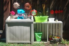 Mud pie kitchen made using crates. I would NOT paint it white, but I love that it can have enclosed storage for all the toys to be put away at the end of play time. (The wind here is brutal and blows plastic toys all over the yard!)