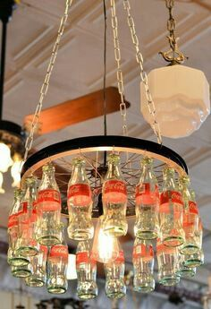 Custom made Coca-Cola chandelier. It is made from a recycled bicycle rim and the small glass Coca-Cola bottles by Cenika: Custom made Coca-Cola chandelier. It is made from a recycled bicycle rim and the small glass Coca-Cola bottles by Cenika: Vintage Coca Cola, Coke Bottle Crafts, Garrafa Coca Cola, Coca Cola Decor, Coca Cola Kitchen, Bottle Chandelier, Wheel Chandelier, Lampe Decoration, Always Coca Cola
