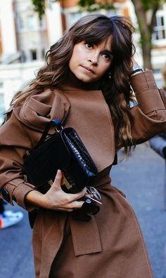 Miroslava Duma in a brown coat holding a black croc Hermès bag