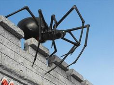 Scary black spider peering over the roof of a building at the Santa Cruz Beach Boardwalk