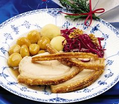 Pork roast (Flæskesteg) with brown pototoes, potatoes and red cabbage served. The Christmas dinner is served on a Royal Copenhagen blue flute half lace dinner plate.