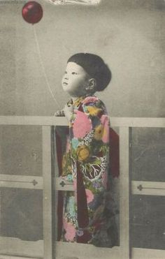 A small Japanese boy holds a balloon while wearing traditional dress in this vintage tinted postcard, c. early 20th century.