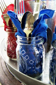 Cute place setting alert: Wrap silverware in repurposed bandanna napkins and display in Mason jar cups for your next barbecue party. See more at A Soft Place to Land.   - CountryLiving.com
