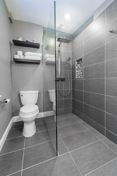 small bathroom with grey flooring, grey tiles in shower wall, grey painted wall in white toilet area, glass panel, wooden shelves on top of the toilet of Small Bathroom with Walk In Shower #bathroomconstruction #remodelingtips