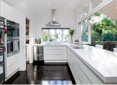 Kitchen - open bifold windows and white cupboards with white benches - walk in pantry