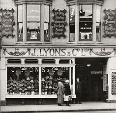 J. Lyons & Co's tea room, Brighton.Two women can be seen admiring the large selection of cakes in the front windows. Joseph Lyons & Co. established in 1808, was one of the largest food manufacturers of the 1900s. The company's tea rooms were hugely popular, especially amongst the working classes. Also known for the care taken in the design & decor of their shops. Lyons & Co's fortunes declined in the late 1960s & in the early 1980s, the company had been broken up & sold.