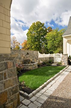 Love the combination of the pea stone, cobblestones and stone wall with built-in fountain. The white picket gate works, too.