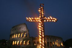 A giant cross is lighted in front of the