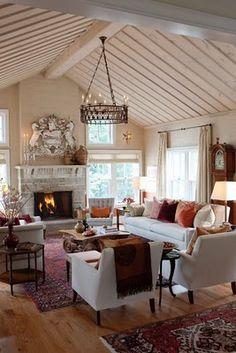 Beautiful living room, beamed and wood slat ceiling painted cream, fireplace, wood floors.