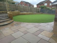 Sleeper retainer wall with artificial grass lawn and grey indian stone patio.