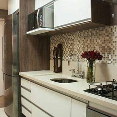 Cozinha de apartamento com pastilhas em tons terrosos, mesclados, e armários brancos e em madeira.