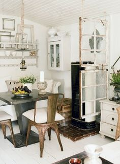 love everything about this room. Window partition, pillow seat cushions on antique chairs, brick flooring under room warmer. I can go on..