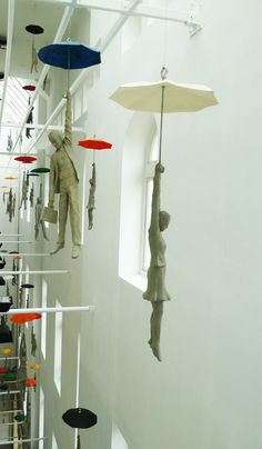These cement figures dangling from umbrellas within a narrow space inside the EBC office center in Prague are part of a installation titled Slight Uncertainty by Czech artist Michal Trpák.