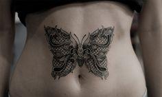 Papillon en dentelle tatoué sur le ventre d'une femme
