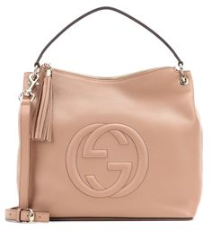 Gucci - Soho leather shoulder bag - With the label's logo stitched on the front with an embossed effect, Gucci's Soho shoulder bag is synonymous with luxury. The roomy tan leather piece is perfect for toting around all your essentials on busy days or long-haul flights. Note the pale gold-tone hardware and exaggerated tassel adding a glamorous finish. seen @ www.mytheresa.com