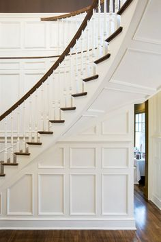 Traditional curved staircase with ornate details and wood paneling
