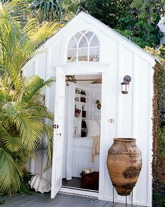 a shed turned into a little guest room! has a full sized bed, chandelier, running water, drapery for privacy.