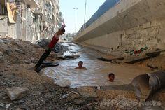 シリア北部アレッポ(Aleppo)で、空爆でできた穴に壊れた水道管からあふれた水がたまってできた「プール」で水遊びを楽しむ子どもたち(2014年7月10日撮影)。(c)AFP/AMC/FADI AL-HALABI ▼16Jul2014AFP|空爆の穴で水遊び、アレッポの子どもたち http://www.afpbb.com/articles/-/3020669 #Aleppo