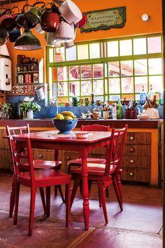 Cocina comedor súper colorida en tonos rojo, naranja y toques de azul y verde. En la casa de la fileteadora Silvia Dotta.