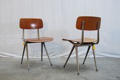 Twee teakhouten (plywood) #Result chairs /schoolstoelen eerste editie jaren 60 met licht grijs frame. De stoelen zijn ontworpen door #FrisoKramer voor Ahrend De Cirkel. Een van de stoelen is gemerkt met stempel. Mooie stoere stoelen met een industrieel en tijdloos karakter