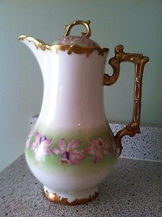 Very nice 9 1/2 Limoges hand-painted chocolate pot. This piece has a pink and lavender floral pattern with gold trim to base, rim, and handle. The floral pattern is hand-painted on a pale green surfa