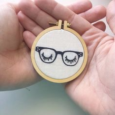Miniature Embroidery Hoop Necklace--Blinking Eyes Hipster glasses A crowd favorite, this hand stitched necklace featuring artsy closed eyes is so fun to wear! Not to mention, how cute are those retro glasses. Its the perfect quirky addition to your outfit; definitely a conversation starter. ________________________________________________________________ ♣ 2 inch mini hoop pendant ♣ Wooden back ♣ Long chain (if you need exact measurements just shoot me a message!) ♣♣PLEASE NOTE: Lobster c...