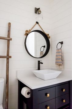 Powder room with shiplap walls, navy vanity and brass hardware. Timber Frame Home with Farmhouse-Inspired Interiors