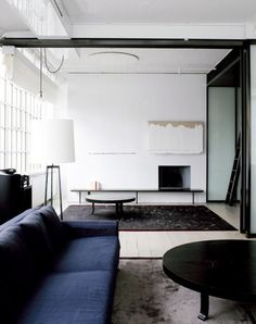 White fireplace with minimalist abstract art above, dark gray sofa, white lamp