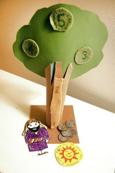 """Zacchaeus two player climbing tree game: Flip a """"tax"""" coin, heads move up one, tails move down one (or not at all).  Playing pieces: Zacchaeus and memory verse sun made out of paper with velcro on back.  Tree made from cardboard tube, painted paper, and felt circle spaces"""