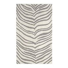 Using wax paper as a stencil, learn how to paint directly onto a cheap rug to create a gorgeous, trendy zebra rug