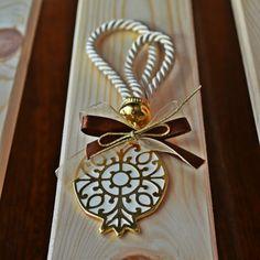 Χειροποίητο ρόδι επίχρυσο με λευκό σμάλτο δεμένο σε ιβουάρ κορδόνι και κορδέλες σε δύο χρώματα.
