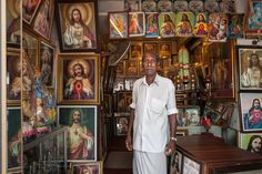 https://flic.kr/p/xUMFLP | Jesus. Kochi, India | Christian religious shop owner inside his store, surrounded by Jesus Christ and Mary portraits of all kinds. Kochi, Kerala, India.
