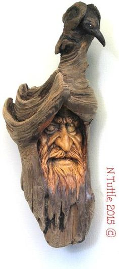 """Raven's Watch""     9½ inches tall and 4 inches at his widest point.  Nature did most of the shaping of the Raven. I did just   a little bit of carving and added some black oil paint.   All carved into a single piece of Oregon driftwood.  Signed and dated:   N. Tuttle 11/7/15"