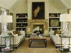 contemporary gorgeous living room with limestone fireplace, white slipcovered sofas with taupe ribbon trim, taupe pillows, Brickmaker's coffee table, round iron glass top accent tables, glass lamps, taupe drapes and built-ins.