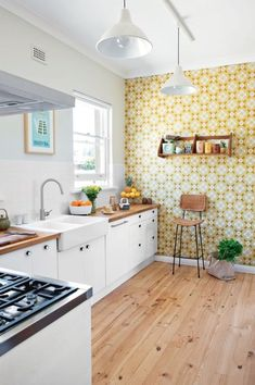 a bold printed wallpaper accent wall is a great idea to add a retro feel to your kitchen