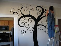 "Even you can paint a tree mural! (tutorial that explains what you need to accomplish this) Then ""hang"" pictures on the family tree!"