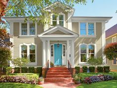 Symmetrical homes evoke a sense of formality, elegance and heritage. Honor tradition with a lighter-colored palette rimmed by darker accents. This home softens into its surroundings, while a bright blue door spotlights the elegant architecture of the entryway. Paint colors: Churchill Hotel Ivory, Betsy's Linen and Lake Breeze by Valspar