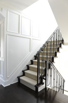 Incredible traditional millwork runs up this stairwell wall and continues down the hallway. The soft white walls contrast against the ebony floors and iron stair railings. A neutral stair runner creates softness under foot up the stairway.