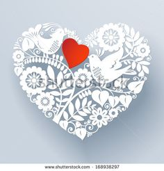 Two love birds are part of a beautiful floral lace like paper cut ornament that creates a three-dimensional heart shape design element.  - stock photo