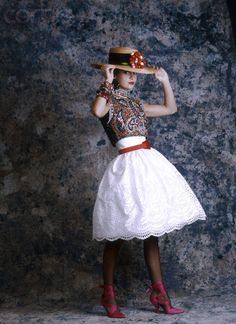 A model wears a Christian Lacroix dress from his 1987 spring-summer haute couture line for Patou. The white dress has a paisley bodice, and is worn with a straw hat.