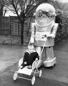 Tinker, a remote-controlled robot, takes a baby for a walk. He could also collect mail and mow the lawn. England 1966