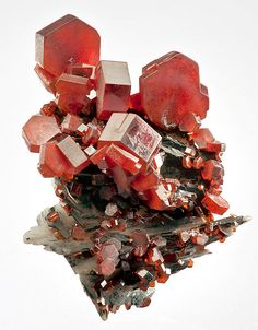 Flashy specimen featuring thick reddish-orange Vanadinite crystals on Barite. From the Mibladen Mine, Mibladene, Midelt, Meknès-Tafilalet Region, Morocco. Measures 4.2 cm by 3.3 cm by 2.9 cm in total size. Ex. Martin Zinn Mineral Collection