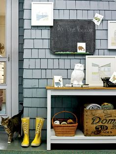 A simple worktable makes this space on an outdoor porch a perfect mudroom with a chalkboard, space for muddy boots, and old crates for handy storage.